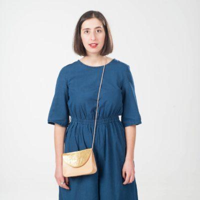 Model mit braun-goldener Leder-Handtasche