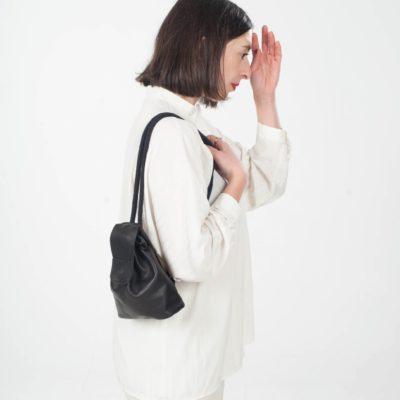 Model mit kleinem schwarzem Leder-Rucksack