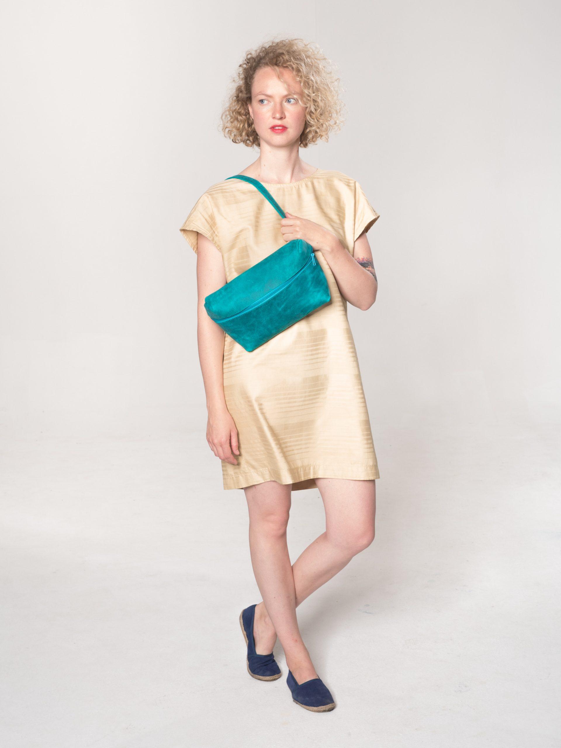 Model mit grüner Leder-Bauchtasche