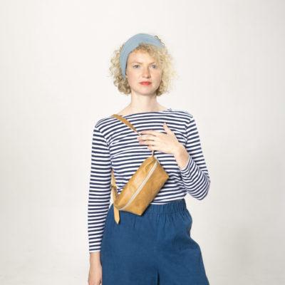 Model mit brauner Lederbauchtasche mit beigem Reißverschluss