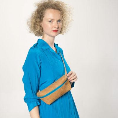 Model mit brauner Lederbauchtasche mit türkisfarbenem Reißverschluss