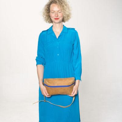 Model mit brauner Lederbauchtasche mit blauem Reißverschluss